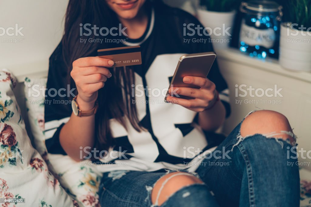 Teenage girl shopping online with credit card stock photo