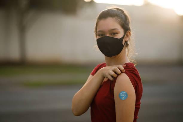 Teenage girl showing her covid 19 vaccine badge stock photo