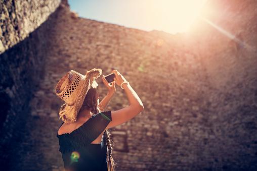 Teenage girl sightseeing italian castle ruins