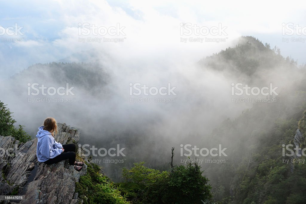 Teenage girl sitting alone in misty Smoky Mountains National Park stock photo