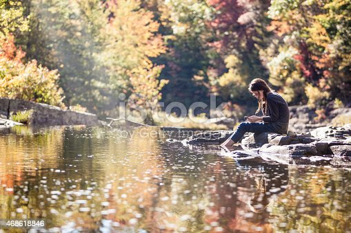 Teenager girl sits on the rock at the Tunkhannock Creek river, in the forest in Poconos, Pennsylvania, and listen the musik with earphones. Austin T. Blakeslee natural area, Tukhannock.