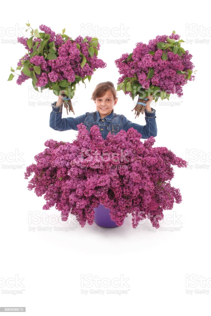 Teenage girl sits with lilac in both hands. stock photo