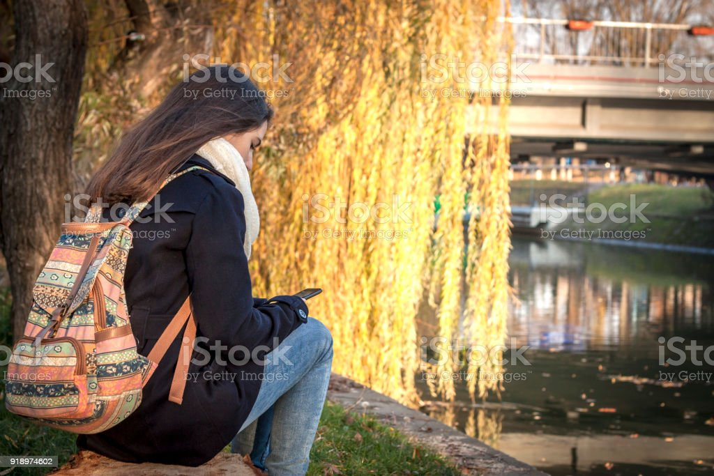 Teenage girl sitting at river bank looking at her mobile phone stock photo