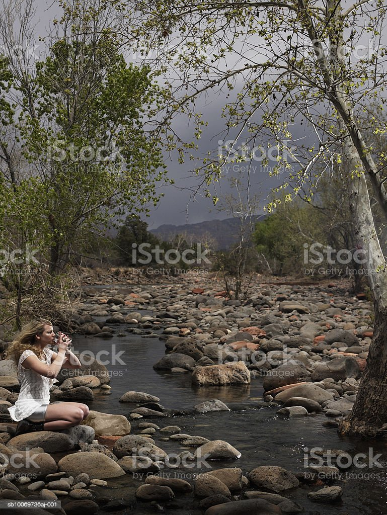 Teenage girl (14-15) sitting besides lake and drinking water royalty-free stock photo