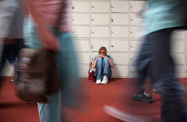 Teenage girl (13-15) sitting by lockers in school hallway stock photo