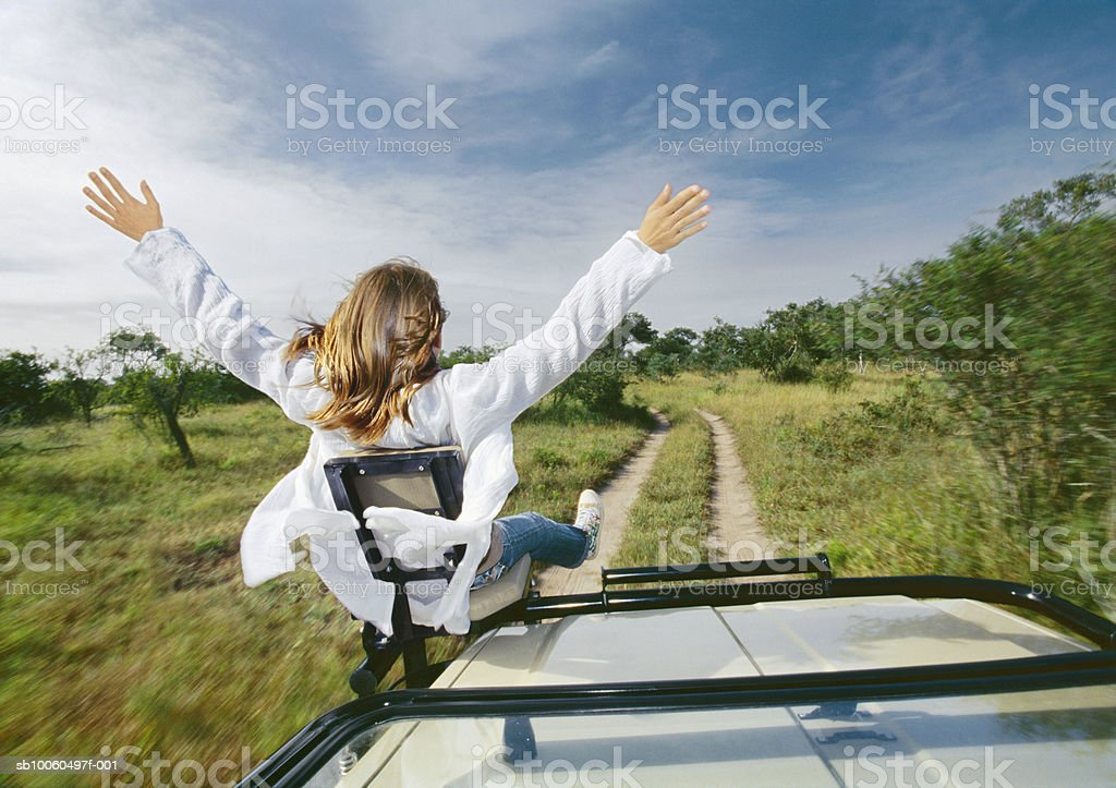 Teenage girl (13-14) sitting on front seat, rear view foto de stock libre de derechos