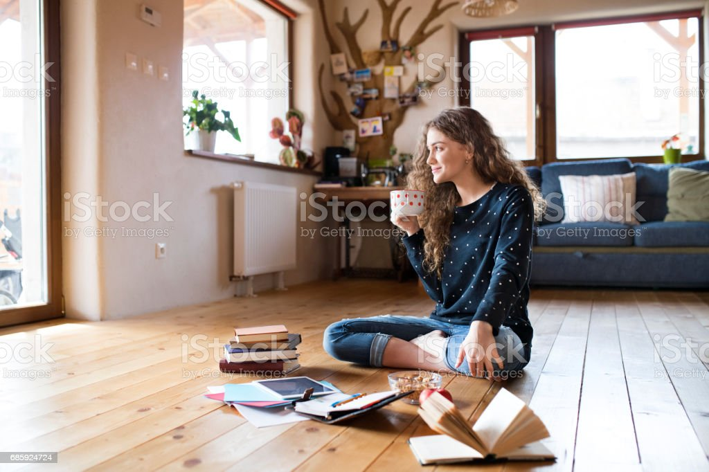 Teenage girl sitting on the floor holding cup of coffee, studying stock photo