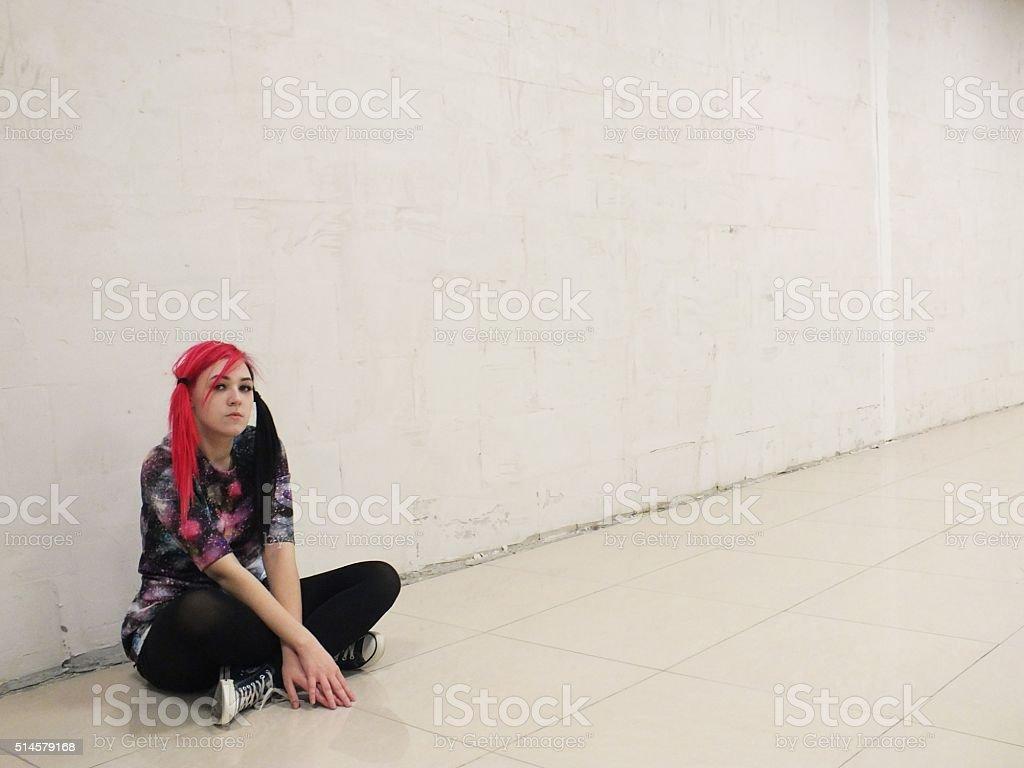 Teenage girl sitting on the floor stock photo
