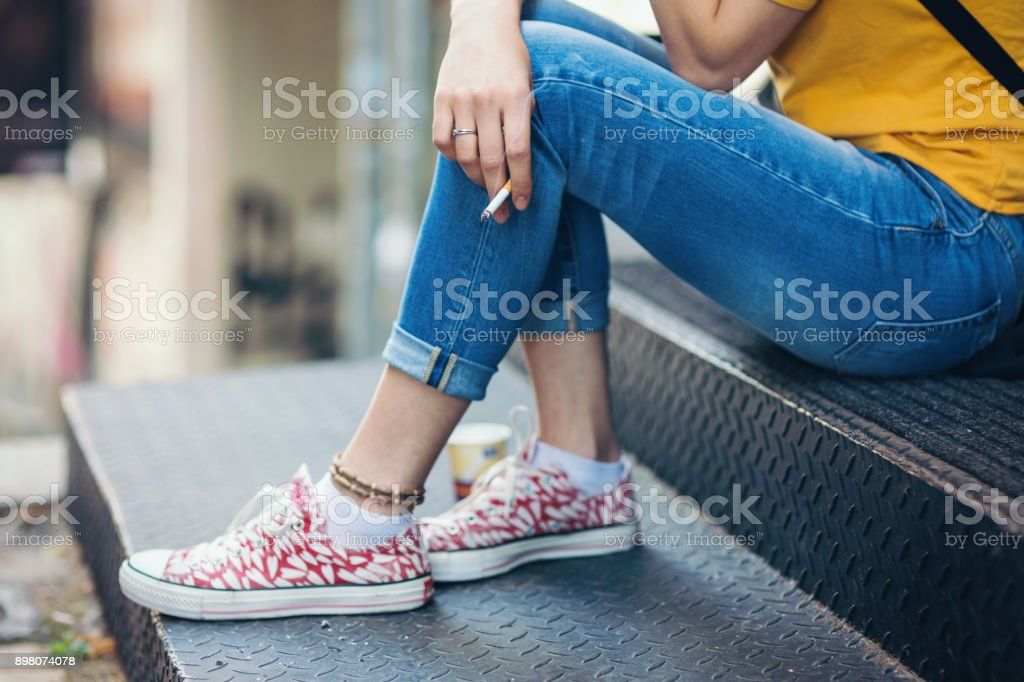 Teenage girl sitting on the staircase outdoors and smoking stock photo