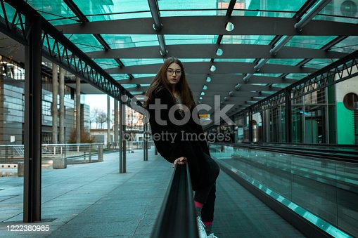 Teenage girl sitting on urban moving stairway, looking serious and confident to the camera. Teenage Urban Lifestlye Portrait.