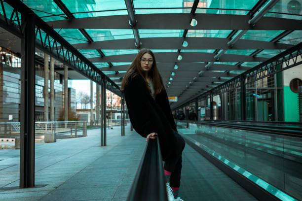 Teenage girl sitting on urban moving stairway stock photo