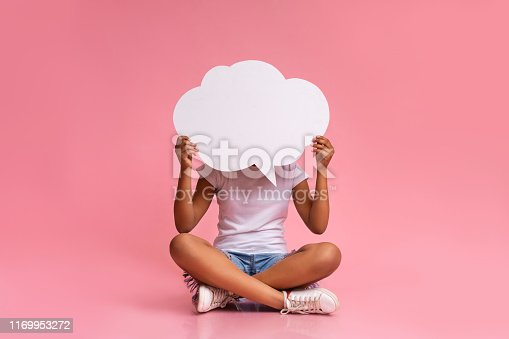istock Teenage girl sitting with crossed legs and holding speech bubble 1169953272