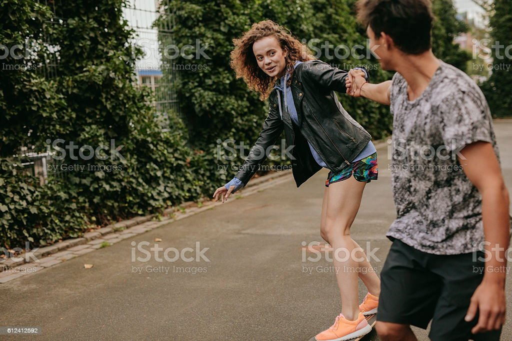 Teenage girl skating on a basketball court with friend - foto de acervo