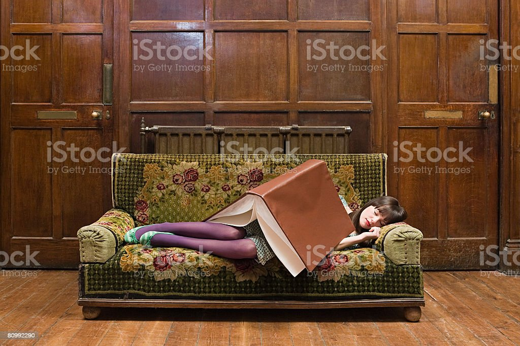A teenage girl sleeping with a large book on her stock photo
