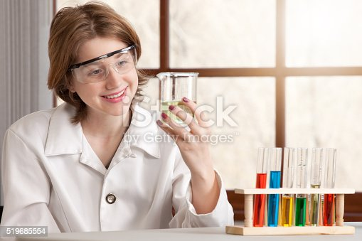 A smiling 14 year old girl observing a liquid in a beaker in chemistry class.