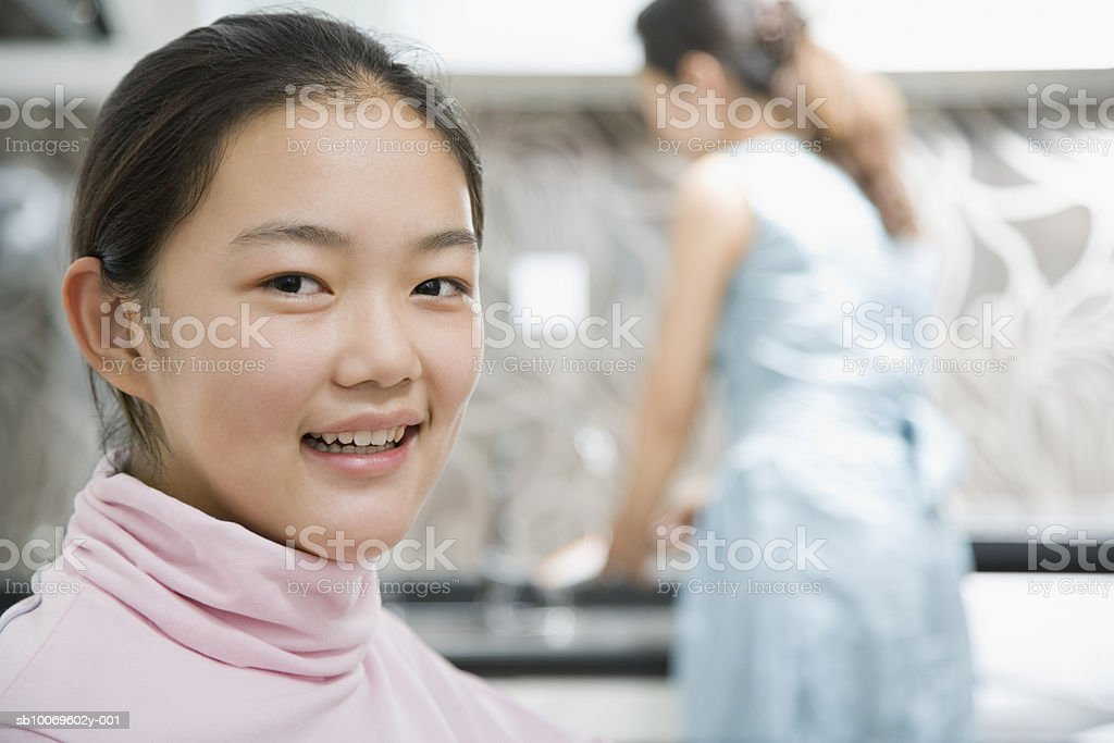 Teenage girl (13-14) smiling, woman in background royalty-free stock photo