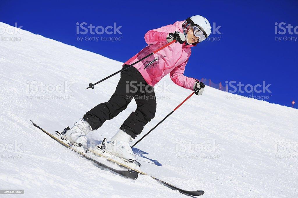 Teenage girl snow skier skiing on sunny ski resorts stock photo