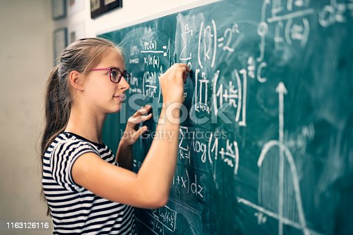 Teenage girl solving mathematical problems. The boy is drawing a graph of a mathematical function. Nikon D850