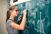 Teenage girl solving mathematical problems. The boy is drawing a graph of a mathematical function.\nNikon D850