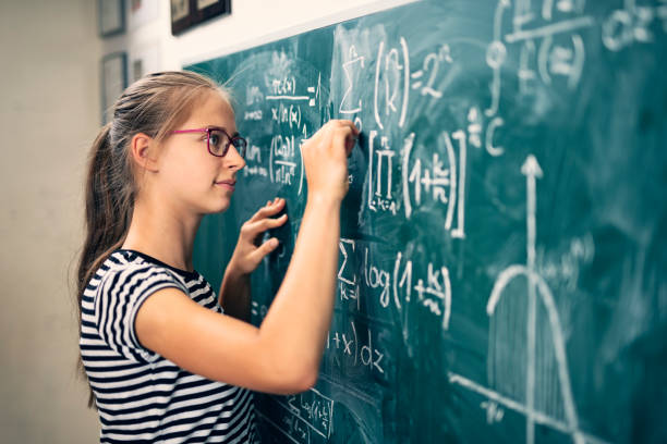 Teenage girl solving advanced mathematical problems Teenage girl solving mathematical problems. The boy is drawing a graph of a mathematical function. Nikon D850 mathematical symbol stock pictures, royalty-free photos & images