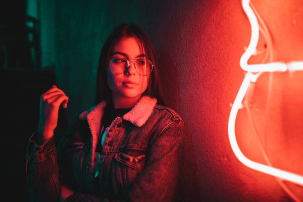 Teenage girl standing next to a neon light stock photo