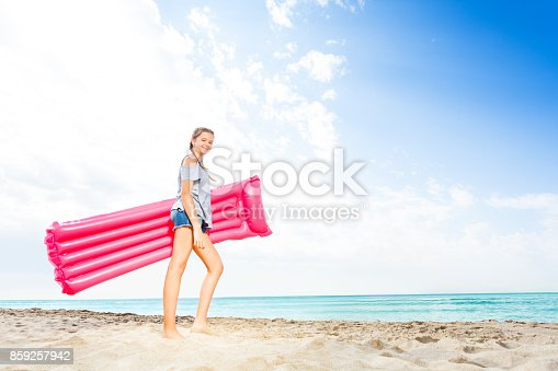 Cute teenage girl standing with matrass on sandy beach against blue sky and sea