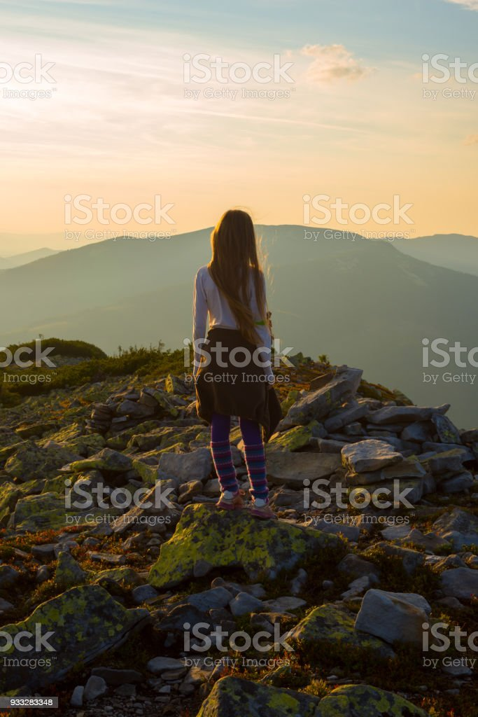 Teenage girl stands on the top among stones during sunset stock photo