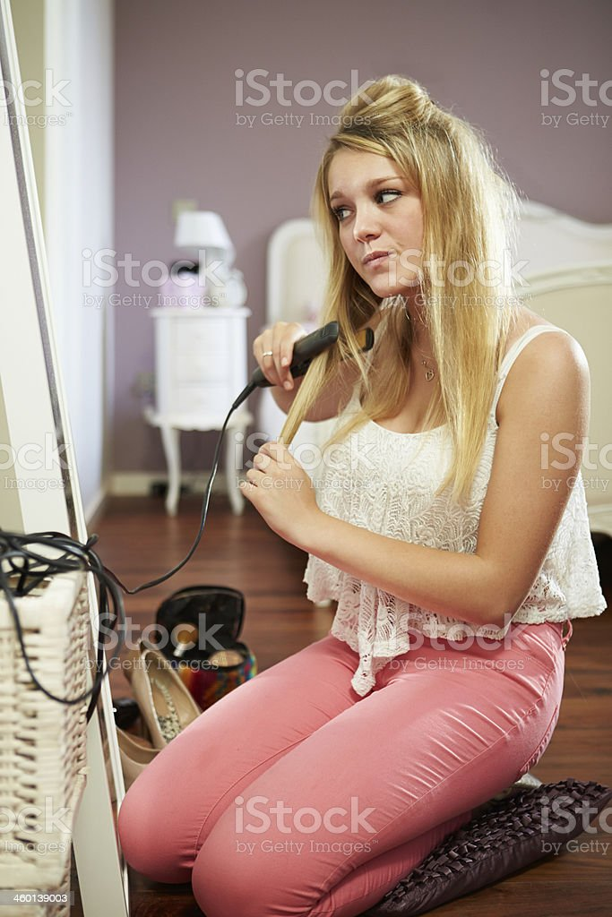 Teenage Girl Straightening Hair In Bedroom royalty-free stock photo