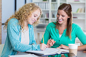 Cheerful tutor works with teenage girl after school. The tutor is helping the girl with a math assignment.