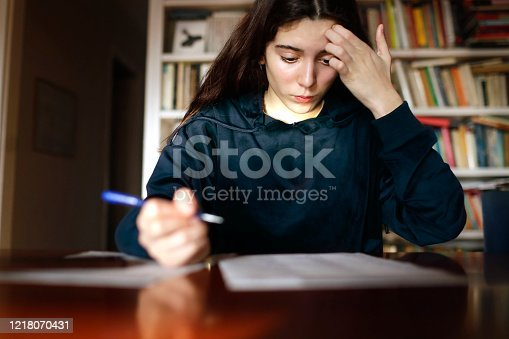 Teenage girl studying in the library, preparing for a test exam