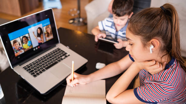 Teenage girl studying with video online lesson at home   family in isolation Homeschooling and distance learning Teenage girl studying with video online lesson at home   family in isolation covid-19. Homeschooling and distance learning desolation stock pictures, royalty-free photos & images