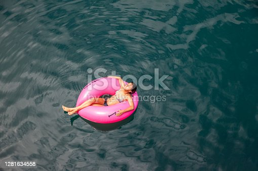 Teenage girl with sun tanned skin swimming on a pink floating inflatable ring at the sea in Madeira island