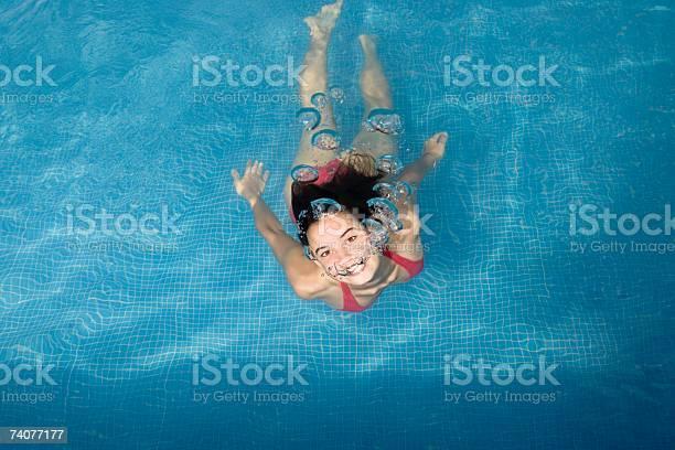 Zwei verspielte Teenager schwimmen nackt und umarmen sich unter Wasser