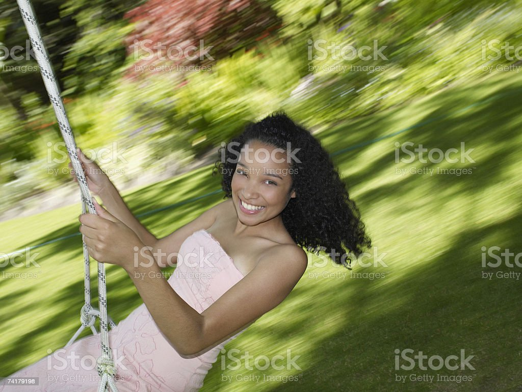Teenage girl swinging and smiling outdoors with motion blur royalty-free stock photo