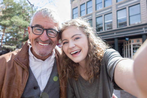 Teenage girl takes selfie with grandfather stock photo