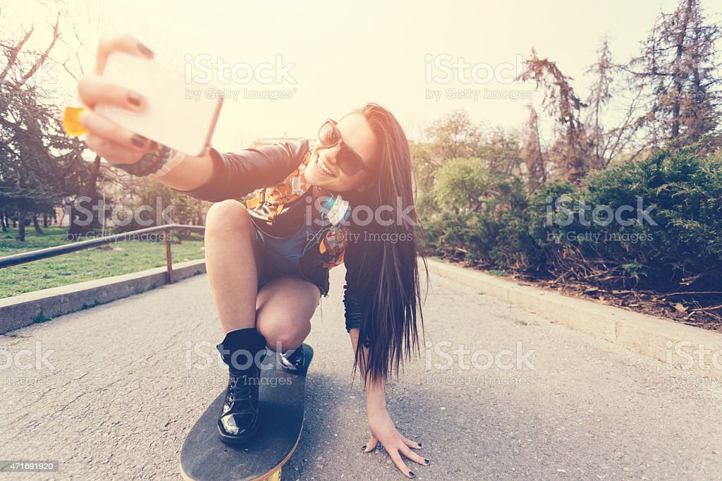 Teenage girl taking a selfie at a skateboard stock photo