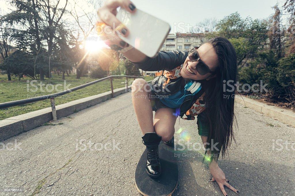 Teenage girl taking a selfie at a skateboard royalty-free stock photo
