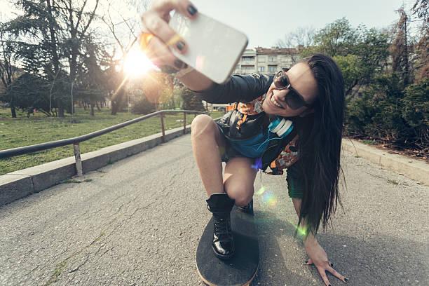 Teenage girl taking a selfie at a skateboard stock photo