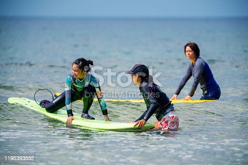 Teenage girl taking a surfing lesson from her mother in Okinawa, Japan