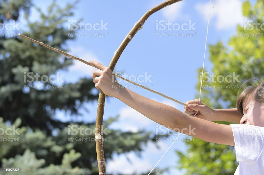 Teenage girl taking aim with a bow and arrow royalty-free stock photo
