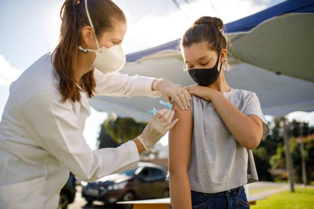 Teenage girl taking covid 19 vaccine stock photo