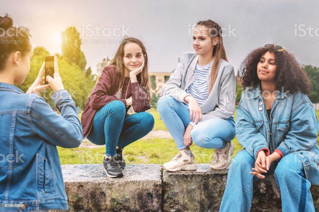 teenage girl taking photo of girlfriends stock photo
