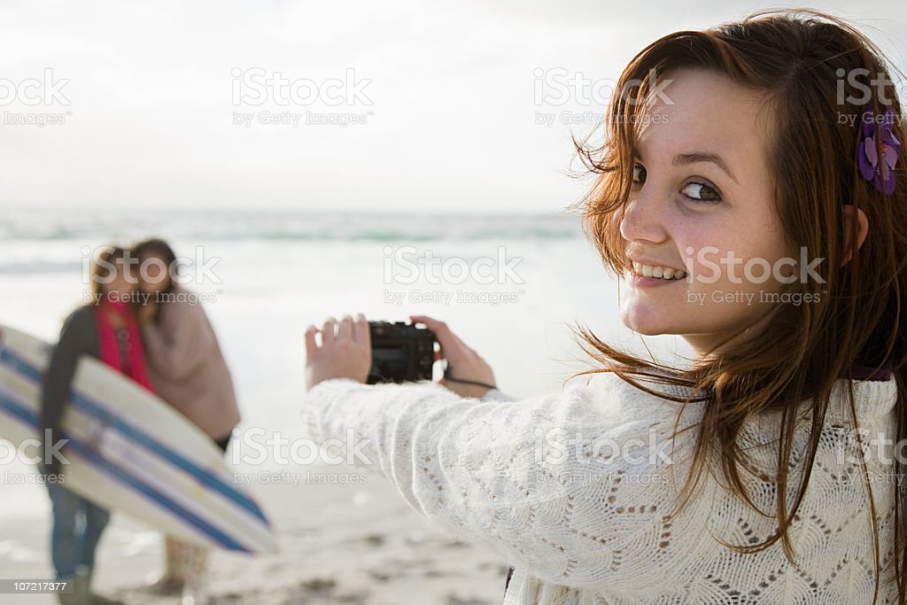 Teenage girl taking photograph of two friends with surfboard royalty-free stock photo