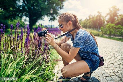 Teenage girl walking in the city park. The girl is using modern mirrorless camera to take photos of beautiful grape hyacinths.