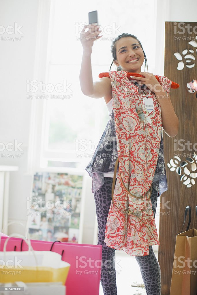Teenage girl taking picture of dress with cell phone royalty-free stock photo