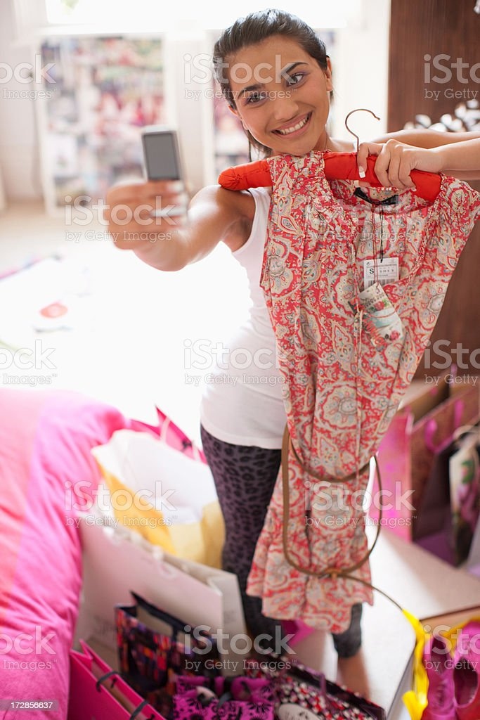 Teenage girl taking picture of dress with cell phone stock photo