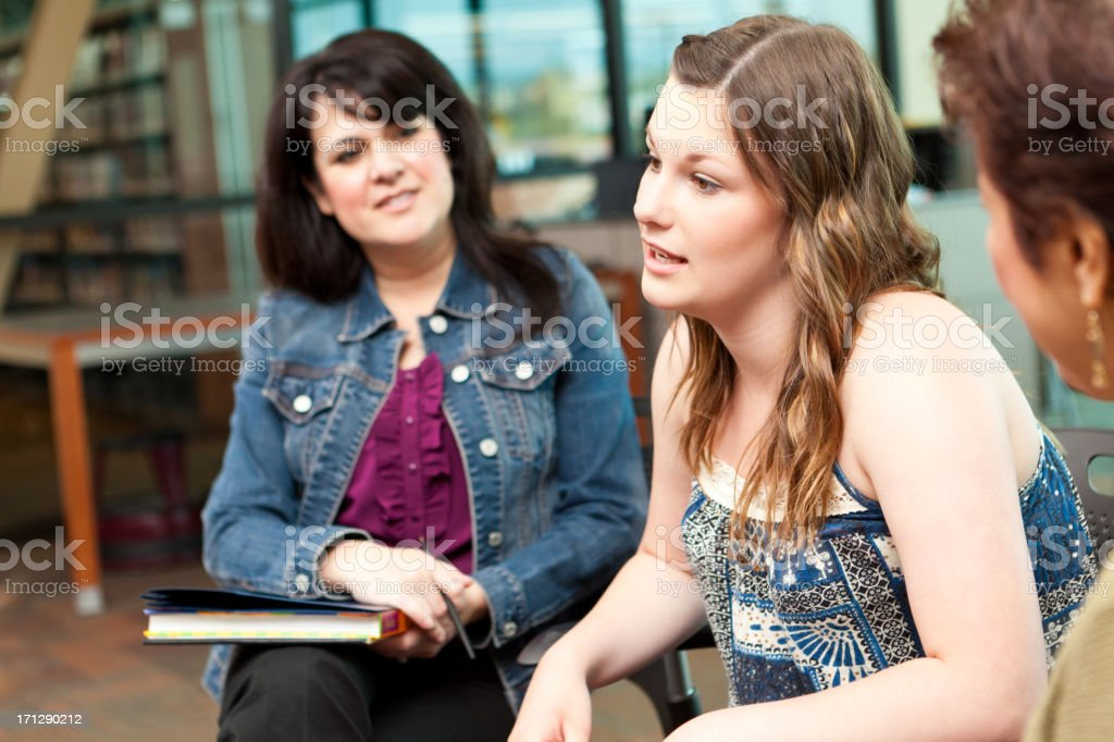 Teenage girl talking to adults in a group discussion setting royalty-free stock photo