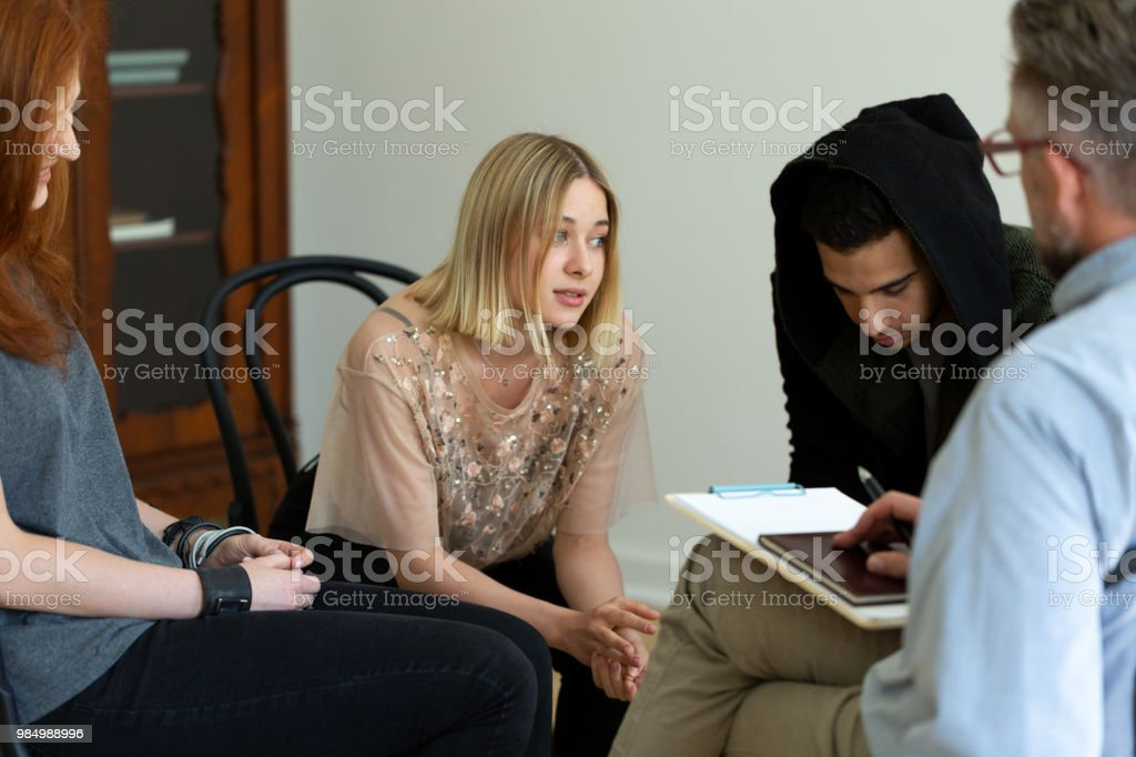 Teenage girl talking with psychologist during meeting of support group Teenage girl talking with psychologist during meeting of support group Addiction Stock Photo