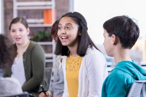 Teenage girl talks during group therapy session African American teenage girl talks about something during support group or group therapy session. cute middle school girls stock pictures, royalty-free photos & images
