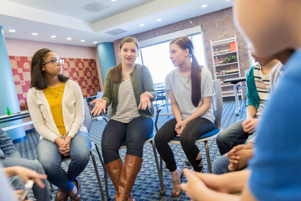 Teenage girl talks during support group meeting Caucasian teenage girl gestures as she talks about something during group therapy or support group session. teenagers only stock pictures, royalty-free photos & images